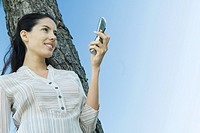 Woman holding cell phone, leaning against tree, low angle view