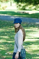 Young woman walking through park, wearing cap, looking over shoulder at camera
