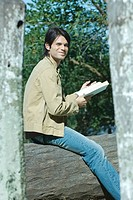 Man sitting on tree trunk outside, reading book (thumbnail)