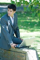 Businessman sitting on low wall in park, using laptop, looking away