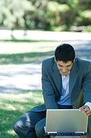 Businessman using laptop outdoors, adjusting screen and smiling