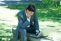 Businessman sitting on low wall in park, using laptop