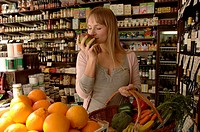 Female customer in delicatessen, smelling mango