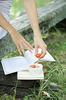 Woman reading book and eating cherry tomatoes, cropped