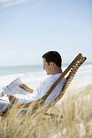 Man sitting in deckchair on beach, reading newspaper
