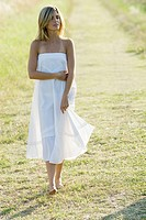 Young woman walking across grass, full length (thumbnail)