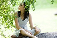 Teen girl sitting on log, under tree, looking away