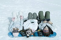 Three sisters lying on snow with heads resting on snowboard