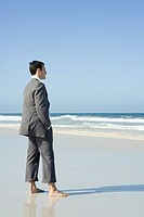 Businessman standing barefoot on beach with hands in pockets, side view
