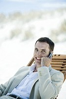 Businessman sitting in deck chair at beach, using cell phone