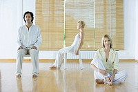 Three adults in various postures in wellness center