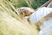 Young woman sleeping in grass, cropped view
