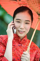 Young woman dressed in traditional Chinese clothing holding parasol and using cell phone