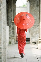 Young woman dressed in traditional Chinese clothing walking with parasol, rear view