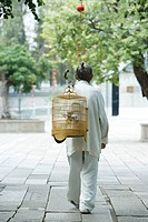 Elderly man in traditional Chinese clothing, carrying bird cage over back, rear view