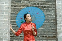 Young woman dressed in traditional Chinese clothing, standing under parasol, looking up