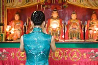 Young woman dressed in traditional Chinese clothing standing at shrine, rear view