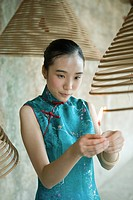 Young woman dressed in traditional Chinese clothing lighting spiral incense hanging from ceiling