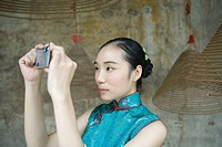 Young woman dressed in traditional Chinese clothing taking photo with digital camera