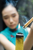 Young woman dressed in traditional Chinese clothing lighting sticks of incense