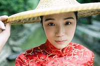 Young woman dressed in traditional Chinese clothing, holding edge of hat