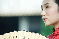 Young woman dressed in traditional Chinese clothing holding fan, cropped view