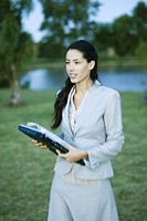 Businesswoman walking through park with laptop