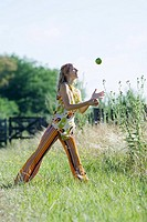 Young woman standing in field with legs apart, juggling apples