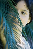 Young woman touching palm leaf, cropped portrait