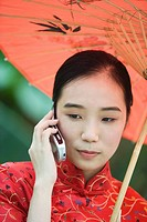 Young woman wearing traditional Chinese clothing, holding parasol and using cell phone