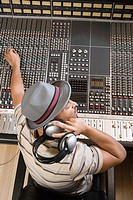 Music producer adjusting sound equipment