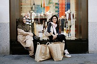 Two beautiful and young moslem ladies sitting in front of the window of a department store, taking a break from a long shopping trip and having their ...