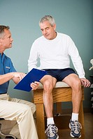 Physical therapist and patient looking at chart