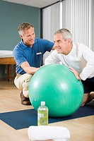 Physical trainer helping man exercise