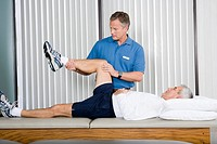 Physical therapist stretching manÆs leg