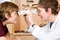 Female optician examining boy