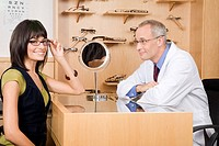 Male optician with woman in office