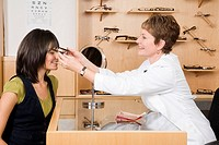 Female optician putting eyeglasses on woman