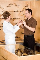 Female optician giving eyeglasses to man