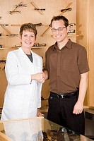 Female optician shaking hands with man