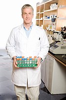 Male scientist holding tray of vials