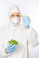 Man in clean suit examining soy beans