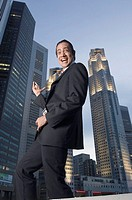 Portrait of a businessman dancing with skyscrapers in the background, Singapore
