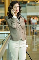 Businesswoman talking on a mobile phone at an airport