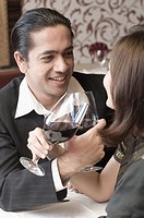 Close-up of a mid adult man with a young woman holding glasses of wine in a restaurant