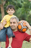 Portrait of a mid adult man carrying his son on his shoulder and holding a soccer ball