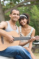Portrait of a young man sitting with his girlfriend and playing a guitar