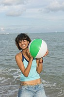 Portrait of a young woman playing with a beach ball on the beach