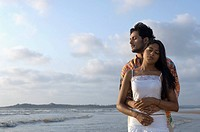 Young man embracing a young woman from behind on the beach