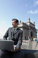 Businessman holding a laptop on his lap with a monument in the background, Gateway of India, Mumbai, Maharashtra, India